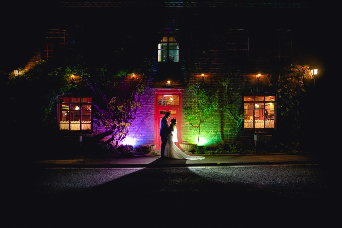 Silhouetted night time photo of a bride and groom in front of The Hundred House Hotel with coloured lights.